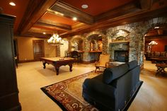 Such a great basement. Love the stone work dividing the areas.