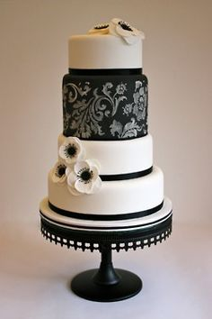 This cake achieves the vintage feel. Pulls in exact black and white flowers from bouquets. Bottom ribbon will be black and white stripes to match the invitations and card box.