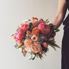 Coral charm peonies, garden roses, and herbs bouquet