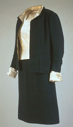 Black Ribbed Wool Day Suit  Designer: Coco Channel (French 1883-1971)  Place Made: France  Date Made: Fall-winter 1956  Medium: Wool, silk satin  Worn by Mrs. John F. Kennedy for a Mark Shaw photographic sitting in Georgetown, Washington, DC, 1958. Also worn during a tour for officials of the American National Theater at the White House, Washington, DC on March 12, 1963.