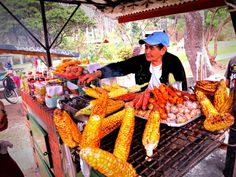 A street vendor selling meat skewers and grilled corn in Parque Nacional, Bogota, Colombia