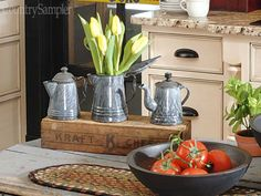 Draw attention to a collection of graniteware coffee pots by lining them up on a wood crate and tucking a bunch of tulips in the center pot. If you don't want to leave standing water in your vessel, outfit flower stems with plastic water tubes.