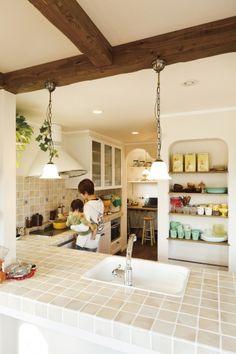 中庭のあるオールドプロヴァンスのおうち  雑貨やアンティークグラスを扱う ショップオーナーの奥さまが重視したのは 中庭とスキップフロア、吹抜けを 取り入れて明るく開放感のあるおうち。 キッチンにはファイヤーキングに似合う イタリアンタイルでハンドメイド、 パインの無垢材と珪藻土で仕上げて素材にも こだわりました♪ 中庭は扉を閉めてプライベートガーデン。 どこにいても家族の気配を感じていられる、 お気に入りのおうちです。中庭のあるオールドプロヴァンスのおうち - かわいい家photo