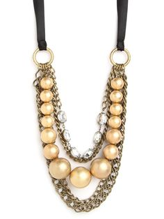 This gorgeous necklace is beyond bold and beyond fabulous. It features cool chunky chain links and gobstopper-sized baubles—both in gold, of course—set against a pretty ribbon. That sprinkling of crystals only adds to the glitz factor.