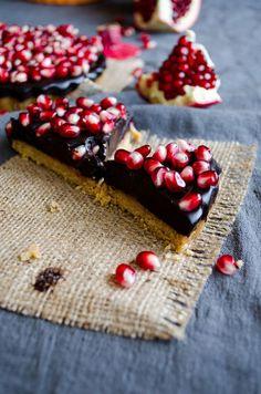 赤いザクロの実がダークチョコレートの上で宝石のようにきれいですね!