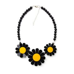 Description Celebrate the arrival of spring with the electric coloured daisy necklace. Bold blooms are laser cut in thick black and yellow perspex that will brighten up your look in an instant. Pair with a patterned dress for a total flower power look.  Measurement 15.5 x 9 cm across Chain Length 48-52cm