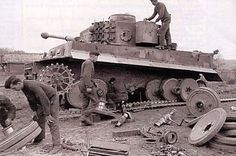 Crews performing maintenance and major repairs to a Tiger 1 in primitive field conditions