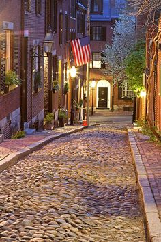 Romantic Boston cityscape photography of old colonial brick row houses along Acorn Street on a beautiful spring evening. Spring blossoms are blooming on Acorn Street near Louisburg Square, the most prestigious address in Beacon Hill. www.RothGalleries.com