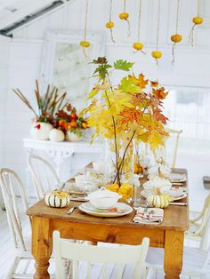 Leaves, gourds, and miniature pumpkins create a pretty fall tablescape, perfect for a harvest party or Thanksgiving dinner.