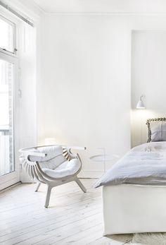 Unusual round armchair in a white Scandinavian bedroom.