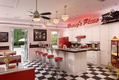 This retro-look pool house celebrates the styles and sensibilities of the 1950s. Black and white checkered floor and vinyl seating sets the scene. The overall palette of red, white and black is characteristic of the time as are the many pieces of memorabilia, including a framed collage of Elvis Presley photographs and an original record album.