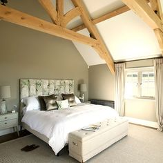 Beige and wood-beamed bedroom. An open ceiling and reclaimed beams makes this bedroom feel bright and spacious. An upholstered floral headboard adds a touch of luxury. #Sleeptember