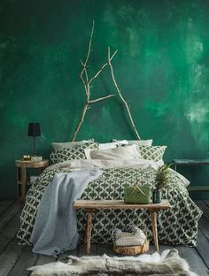 Rich green bedroom with gorgeous wall and patterned bedding - boho design: