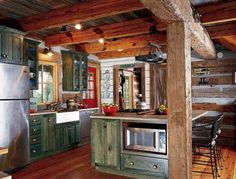 Log cabin with distressed cabinets add to the rustic charm.