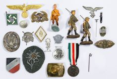 Lot 343: World War II German Badge and Pin Assortment; Including an Africa Corps pin, a metal Edelweiss flower on green wool, a skull pin, three Elastolin German lead toy soldiers; together with a US Marine belt buckle