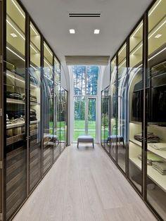 Walk-in closet com portas de vidro e sensação de ampliação pela vista do jardim.
