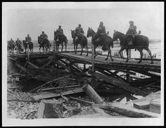 A troop of cavalry in single file crossing a fairly makeshift wooden bridge. The ruins of the iron and stonework of the original bridge can be seen in the water. Bridges were commonly destroyed in order to delay opposing troops. The Royal Engineers were responsible for providing temporary bridges as fast as possible.  The cavalry are riding with their full kit. Their rifles are hung on the right side of the horses, ready for action. Much of the rest of their kit is carried behind the saddle…