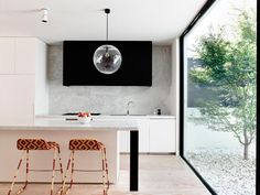 Love the black hood against the marble backsplash. That huuuge window is super, it's like cooking outdoors inside! The colorful bar stools add an interesting edge.