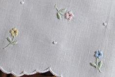 Toalha em linho bordada com viúvas, garanitos e ponto corda. Mais