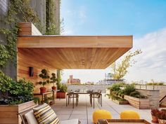 For the sprawling rooftop terrace of a Manhattan penthouse, Greg Dufner and Daniel Heighes Wismer of design firm Dufner Heighes devised a cantilevered mahogany awning and coordinating planters; the sconces are from YLighting, the tables and chairs are by Richard Schultz for Knoll, and the poufs are by CB2. The plantings were designed by the Brooklyn-based landscape firm Future Green Studio. | archdigest.com