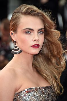 At the Search premiere at Cannes, Cara Delevingne's hair was swept to one side, while her makeup was a mix of smoky shadow and a brick-red lip.
