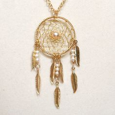 Dream Catcher Pearl & Gold Dreamcatcher Necklace with Feathers. $27.00, via Etsy.