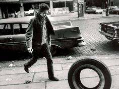 """1963, Greenwich Village, NY– Bob Dylan.  Much has been made about why Dylan chose to roll a tire for this photo shoot in New York in 1963.  But Marshall insists there was no cryptic reasoning for it. """"He just picked up a tire that was nearby and rolled it, that's the end of it.""""  –Photography by Jim Marshall"""