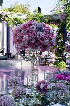 A pomander of roses and hydrangeas in shades of pink and purple tops a silver candelabrum.