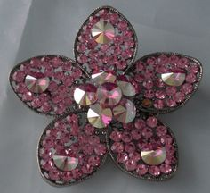 """Pink Flower Floral Jeweled Figural Vintage Pin. Pink jeweled stones in a silver inlay. Flower pattern with larger stones in the center and one on each petal. Silver toned backing. Measures 2.75"""" around."""