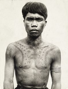 657274. An Ifugao tribesman ornamented with tattoos and bicep bangles.