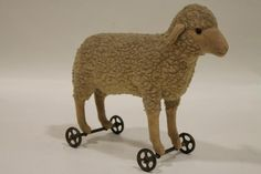 """Sold For $ 1,250   Mohair lambs wool, felt face legs and ears, shoe button eyes, metal wheels and axles, straw-filled body, button in ear, 8 1/2"""" high x 10"""" long.                            Condition report           Good - Small areas of worn coat"""
