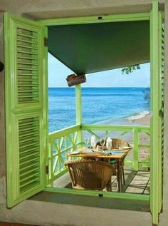 Lovely view of turquoise water thru green shutters.
