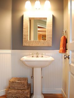 This cottage powder room gets an updated look with white wainscoting, a modern mirror, and a pop of orange in the towels. The stacked baskets on the floor are a great way to house bath products when using a pedestal sink. Clever Bathroom Storage, Bathroom Organization, Organization Ideas, Toilet Storage, Bathroom Shelves, Washroom, Bathroom Cabinets, Bathroom Vanities, Downstairs Bathroom