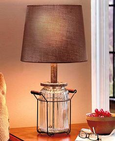 This Glass Jar Lamp lights up any room while adding a vintage accent to your space. It features a large, rippled glass jar that rests inside a simple metal base. The base has 2 wooden handles to help you move it around the room. Neutral color of the lamp