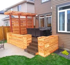 Custom composite deck with cedar horizontal privacy and arbor top with cypress planter boxes and lighted stairs.