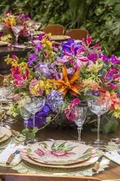Ao centro das mesas dispomos os arranjos mais lindos e irretocáveis feitos por Marcinho Leme, da Milplantas, com rosa do jardim, hortênsia, orquídea vanda, gloriosa, chuva-de-ouro, bromélia, alecrim, lavanda, e flor de alcachofra.