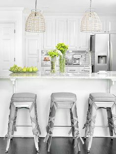 All-white kitchen cabinets with silver accents in the chairs and the backsplash; also love the cabinet hardware