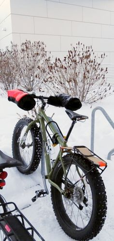 Notice the bicycle's handlebars. Insulated mittens designed for cold weather to keep your hands warm during a winter bike ride! These are handlebar mitts, also called bike pogies.