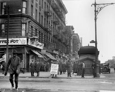 Crowd gathers near a subway kiosk on a Harlem street corner in the 1920s