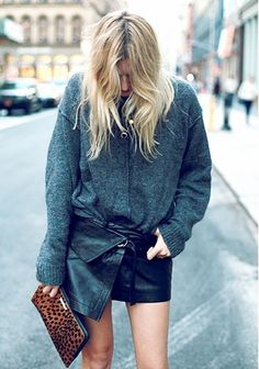 Camtyox tucks her slouchy sweater into an asymmetrical leather skirt, and carries a leopard clutch.