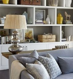 Chic living room with white built-ins with backs of shelves painted taupe gray, white  yellow ginger jars, hammered metal gourd lamp and blue sofa and blue pillows. by roxanne