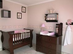 Scruffy bear nursery decor - walls painted neutral with pink/stone wall border, the room is complemented with dark wood furniture for a classic look.