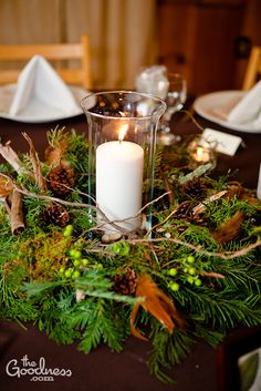 Festive centerpiece designed in a wreath style, with pillar candle in the center. As seen $75 www.visualimpact-design.com
