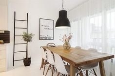 wood dining table, white chairs, black oversized fixture