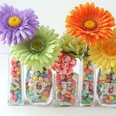 gerber daisies in different glass bottles filled with pastel candies, with letters spelling spring