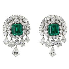 VAN CLEEF & ARPELS • Each of these magnificent Van Cleef & Arpels earrings features a large, center emerald-cut emerald surrounded by round-cut diamonds, with dangling pear-shaped diamonds adding drama to the 18K white gold setting. Accompanied by certificates stating that the emeralds are Colombian, and untreated. Circa 1990s
