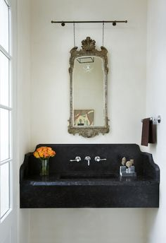 Incredible powder room with floating black sink with matching backsplash framing the wall mounted faucet below an antique…