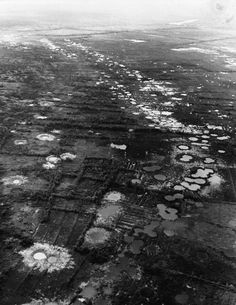 Henri Huet - Water-filled bomb craters from B-52 strikes against the Viet Cong mark the rice paddies and orchards west of Saigon, Vietnam, 1966.