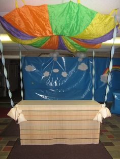 Front Registration table for Sky VBS.  I used a classroom parachute and attached it to the ceiling with fishing line, sewn 4 weight bags and used a window blind for the hot air balloon front!