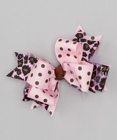 Bold and bright, this pretty bow is a quick way to add fashionable flair to unruly hair. Layers of vibrant ribbons speckled with perky prints are topped with a decorative button for a look that's worthy of everyday wear.4'' WPolyester grosgrainMade in the USA